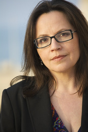 A photo of the author, Shannon McKenna, with her head tilted to the left